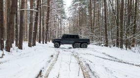 在冬天路之前乘坐在积雪的森林里的SUV 6x6的看法 免版税图库摄影