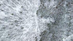在冬天路之前乘坐在积雪的森林里的SUV 6x6的鸟瞰图 免版税库存图片