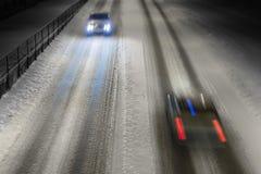 在冬天路的两辆汽车 免版税库存照片