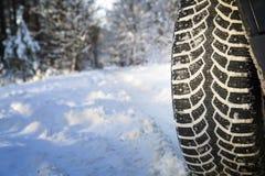 在冬天路的汽车在木头 免版税库存照片