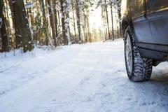 在冬天路的汽车在木头 库存照片