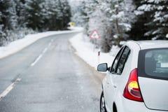 在冬天路的白色汽车 库存图片