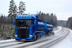 在冬天路的蓝色斯科讷槽车 免版税库存图片