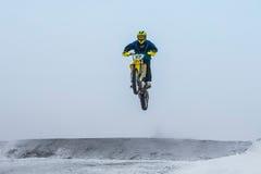 在冬天路的跳高和飞行运动员摩托车 库存图片