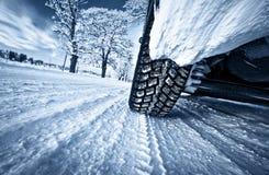 在冬天路的车胎 免版税库存照片