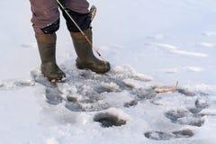 在冬天钓鱼的孔前,只有渔夫的腿 图库摄影
