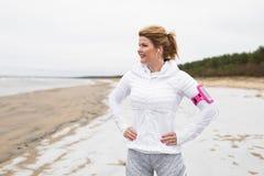 在冬天锻炼前的妇女在海滩 库存图片