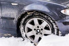 在冬天随风飘飞的雪的汽车 免版税库存图片