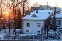 在冬天雪的晚上太阳在房子里 图库摄影