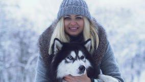 在冬天雪背景中的俏丽的年轻女人画象拿着和拥抱蓬松西伯利亚爱斯基摩人 狗在一个冬天 股票视频