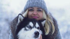 在冬天雪背景中的美丽的年轻女人画象拿着和拥抱蓬松西伯利亚爱斯基摩人 在a的狗 股票录像