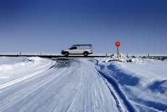 在冬天雪道的交叉点停车牌 库存图片
