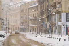 在冬天雪风暴期间的坚硬交通在街市布加勒斯特市 库存图片