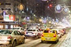 在冬天雪风暴期间的坚硬交通在街市布加勒斯特市 库存照片