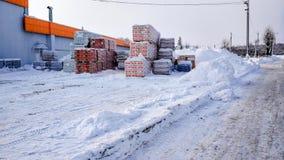 在冬天露天储藏商店在城市 有水泥和油灰的大袋在一个木板台,打开的  免版税库存照片