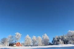 在冬天风景的小红色客舱 免版税库存照片