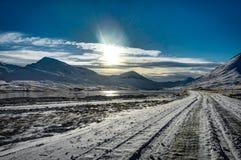 在冬天风景视图的冰岛积雪的街道与蓝色s 库存照片