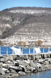 在冬天风暴S期间,有花边的冰帷幕在岩石码头形成了 免版税库存照片