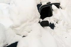 在冬天飞雪困住的被放弃的积雪的汽车 库存照片