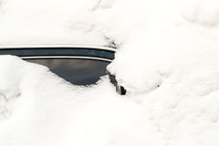 在冬天飞雪困住的被放弃的积雪的汽车 免版税库存照片