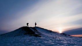 在冬天高涨在山,登山家期间,两个旅行家现出轮廓与背包互相显示照相机 股票录像