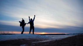在冬天高涨在山,登山家期间,两个旅行家现出轮廓与背包互相显示照相机 股票视频