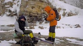 在冬天高涨期间,在河岸停下来的两个徒步旅行者有休息和喝一些热的茶 股票录像