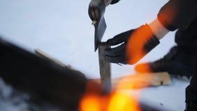 在冬天,一个砍与一个轴的人佩带的手套木头在火背景  股票视频