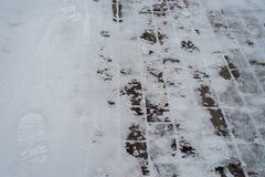 在冬天,一个积雪的铺的块在城市 从起动的脚印在雪 边路在的冬天 图库摄影