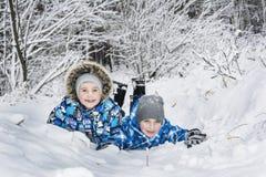 在冬天,在一个冷淡的森林,愉快的男孩在雪说谎 库存图片