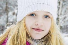 在冬天,在森林里,有a的一个美丽的小女孩 免版税库存照片