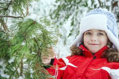 在冬天,在森林,一个小美丽的女孩在别针附近站立 免版税库存照片