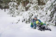 在冬天,积雪的杉木森林男孩在随风飘飞的雪附近说谎 免版税图库摄影