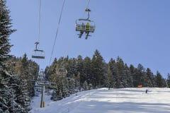 在冬天-冬季体育概念期间,在意大利滑雪区域的驾空滑车在积雪的阿尔卑斯和杉树 免版税库存照片