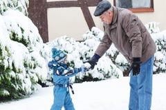 在冬日的祖父和小孩男孩 免版税库存照片