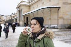 在冬时,喝从有治疗矿泉水的杯子的少妇在自然温泉在卡洛维变化 免版税库存图片