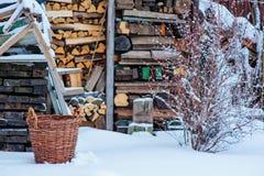 在冬景花园的木头流洒的土气火和篮子 免版税库存照片