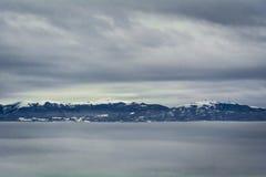 在冰冷的纯净冬天天空新芽的积雪覆盖的山从云彩海  免版税库存照片