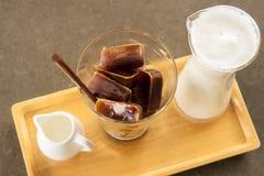 在冰块形状的咖啡用蒸汽牛奶和糖浆 免版税库存照片