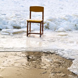 在冰孔边缘的冰封椅子在冻湖 免版税库存图片