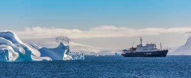 在冰山中的蓝色巡航船与冰川在背景中 免版税图库摄影