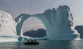 在冰山曲拱,格陵兰前面的可膨胀的小船 免版税库存照片