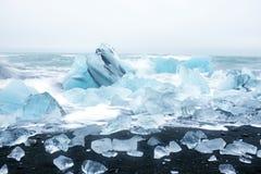 在冰岛冰在一个黑沙子海滩的岩石 库存照片