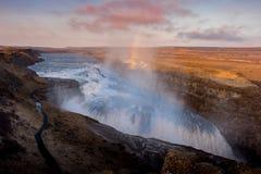 在冰岛日落的古佛斯瀑布瀑布与彩虹和多云天 免版税库存照片