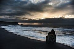 在冰岛黑色沙子海滩的早晨日出与海洋水波和风雨如磐的云彩 飞鸟在背景中 Vik Vikurbraut 库存图片