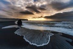 在冰岛黑色沙子海滩的早晨日出与海洋水波和风雨如磐的云彩 Vik Vikurbraut 免版税库存图片
