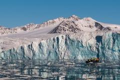 在冰川,斯瓦尔巴特群岛前面的可膨胀的小船 免版税库存照片