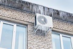 在冰柱的房子的屋顶和空调 免版税图库摄影