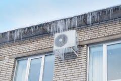 在冰柱的房子的屋顶和空调 库存图片