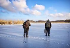 在冰池塘等待的受害者的猎人 免版税库存照片